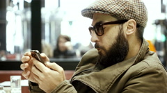4K, hip,stylish intellectual man in city cafe using his smartphone - stock footage