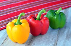 Yellow, red and green capsicum on a wooden table Stock Photos