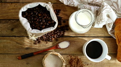 Top view of breakfast scene with cup of coffee, coffee beans, milk and croissant Stock Footage