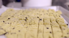 Woman Sprinkles Sugar Over Sliced Cookie Dough On Cookie Sheet Stock Footage