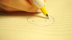 Young woman drawing a smiley in her planner. Shallow focus macro video Stock Footage