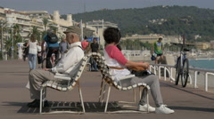 Young and old people sitting on benches on Nice promenade Stock Footage