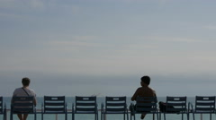 Two men sitting and admiring the Mediterranean Sea in Nice Stock Footage