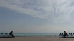 Two people sitting and admiring the Mediterranean Sea in Nice Stock Footage