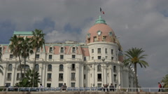 People sitting and walking near the Le Negresco Hotel in Nice Stock Footage