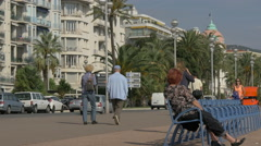 People driving, riding bikes, walking and sitting on benches on Nice promenade Stock Footage