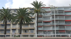 Three palm trees in front of buildings on Nice promenade Stock Footage