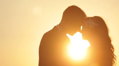 Silhouette of beautiful wedding couple kiss on the sunset close up - stock footage
