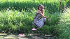 Girl in nature near lake with lilies and paddy field in Bali, Indonesia Stock Footage