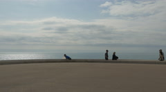 Tourists walking by the sea on a cloudy day in Nice - stock footage