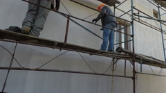 Two builders mounted scaffolding. - stock footage