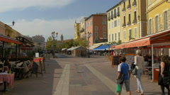 Outdoor restaurants on a street in Nice on a sunny day - stock footage
