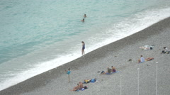 Tourists relaxing on the rocky seashore of Nice Stock Footage