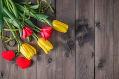 Spring tulip flowers on dark wooden table - stock photo