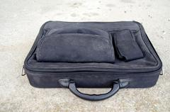 Old dusty laptop bag on cement - stock photo
