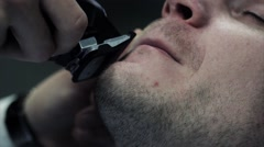 The barber carefully makes a haircut beard with trimmer - stock footage