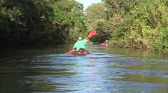 Rear view shot of canoes rowing along river. - stock footage