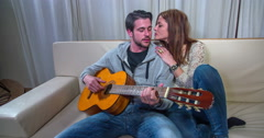 Stock Video Footage of Young man is playing a guitar and his lady kisses him on his cheek