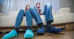 Stock Video Footage of Young couple tapping with their slippers when watching tv