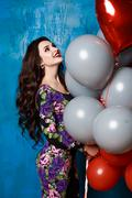 Brunette holding balloons and have fun at the feast - stock photo