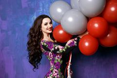 glamour lady  keeps air red and white balloons - stock photo