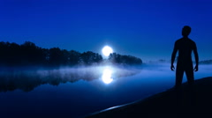 The man stand on the river bank on a background of light of the moon. Time lapse - stock footage