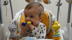 Seven-month baby playing automatic electric swing Stock Footage