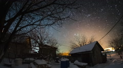 Time lapse of the starry sky in the winter garden with buildings and trees Stock Footage