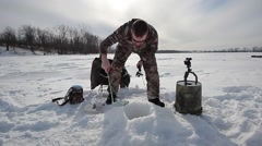 Ice fisherman removes slush from hole Stock Footage