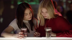 Beautiful girl is typing on her smartphone at bar Stock Footage
