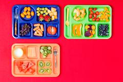 Three kids lunch trays with fruit - stock photo