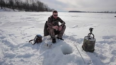 ice fishing man in camo - stock footage