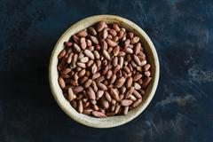 Roasted peanuts in wooden bowl - stock photo