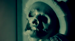 Creepy human skull in shadows - horror background, seamless loop, transition Stock Footage