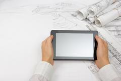 Stock Photo of Architect working on blueprint. Architects workplace - architectural project