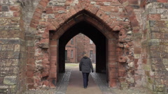 Carlisle England woman walks through castle gate entrance 4K Stock Footage