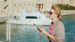 A female tourist enjoys the tablet on the background of yachts Stock Footage