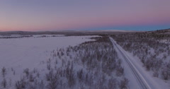Frozen Road In The Arctic With A Few Small Trees and Purple Sky Stock Footage