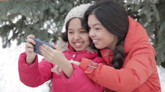 Smiling two girl taking a selfie with smartphone outdoors in warm clothes Stock Footage