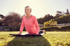 Healthy senior woman in a yoga pose with gentle sunflare - stock photo