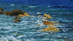 Waves breaking on rocks on a sunny day Stock Footage