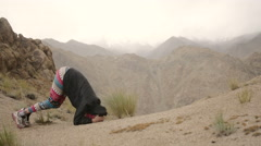 Yoga girl doing headstand in mountains in rain Stock Footage