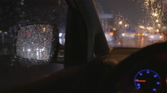 The reflection of the rainy city in the left mirror of a car. Evening-night time - stock footage