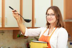 Woman with ladle and pot in kitchen - stock photo