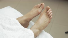 Not moving woman feets under white blanket in beauty saloon. Patient Stock Footage