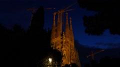 Sagrada Familia at night time, dim illuminated against dark blue sky Stock Footage