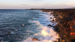 Waves crash on golden cliffs at sunrise, coastline in perspective (4K) Stock Footage