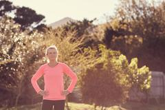 Active senior woman wearing sporty top in morning sunlight - stock photo