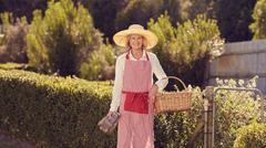 Senior woman in gardening gear at her backyard gate - stock photo