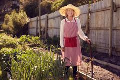 Senior woman with gardening tool in a vegetable garden Stock Photos